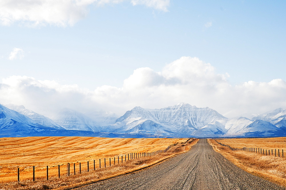 Gravel Road Between Farm Fields And Rocky Mountains In The Distance, Pincher Creek, Alberta, Canada