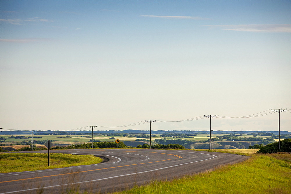Electrical Wires Along A Curving Road With Farmland In The Distance, Saskatchewan, Canada - 1116-46433
