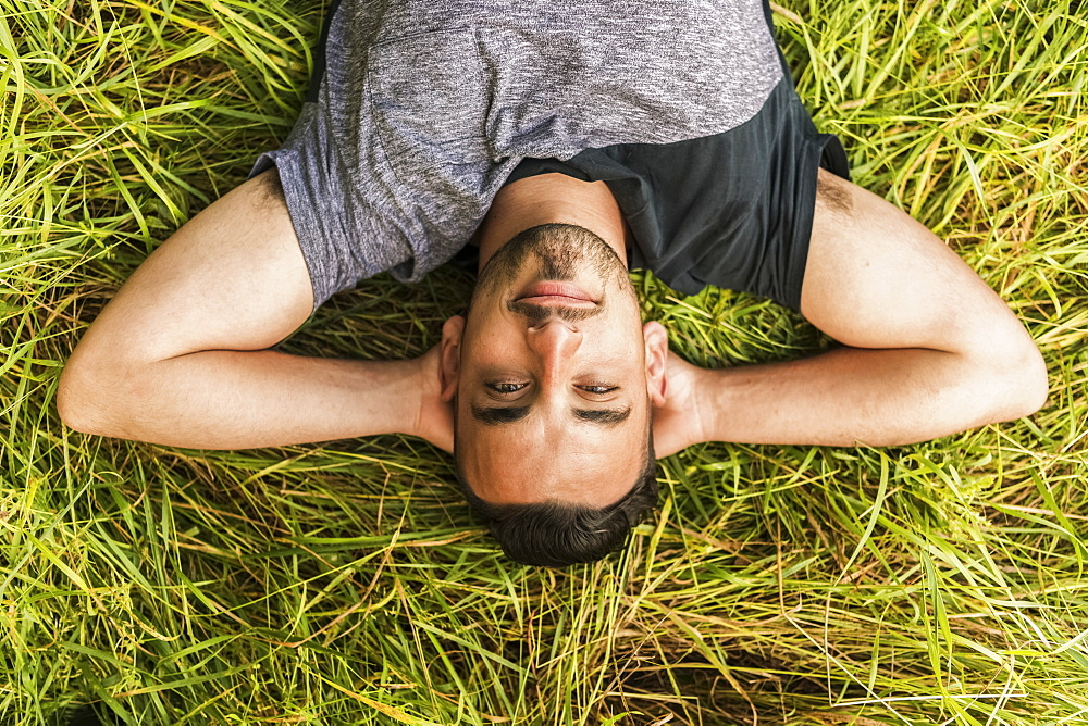 Close Up Of A Man Laying On The Grass With His Hands Behind His Head, Reigate, England