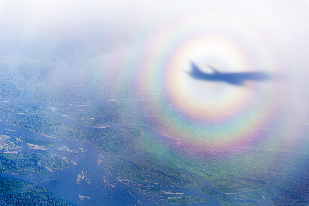Aerial View Of The Shadow Of A Commercial Airline In The Middle Of A Sundog Over A Cloudy North Slope Tundra, North Slope, Alaska, United States Of America