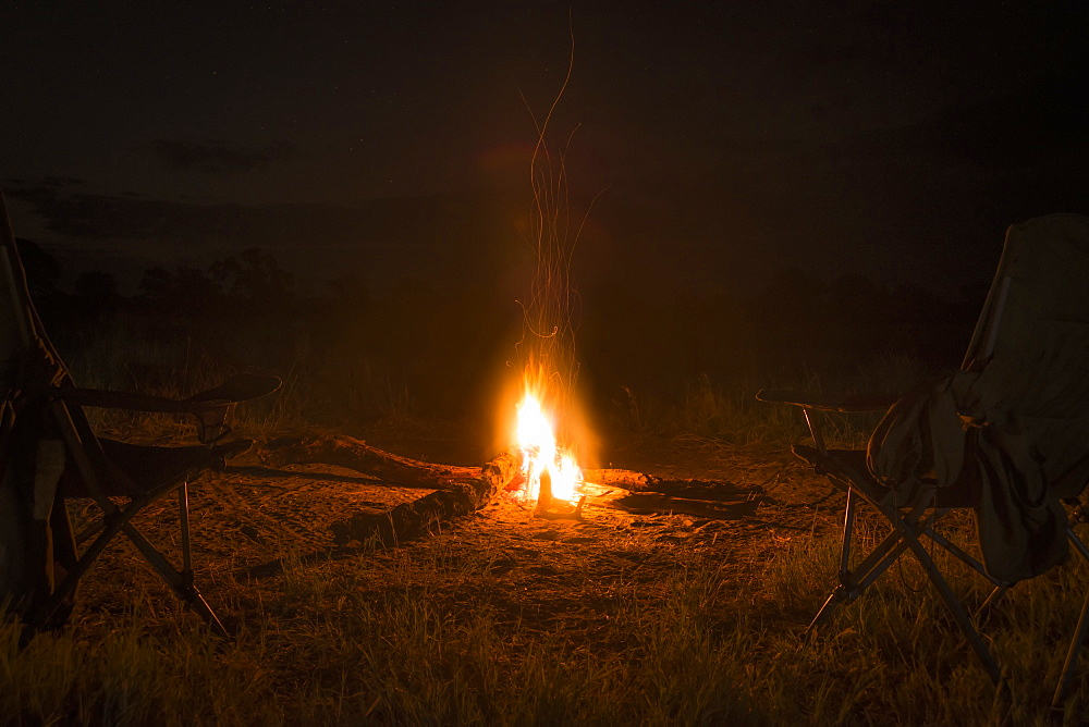 Two Camp Chairs Around Fire At Night, Botswana