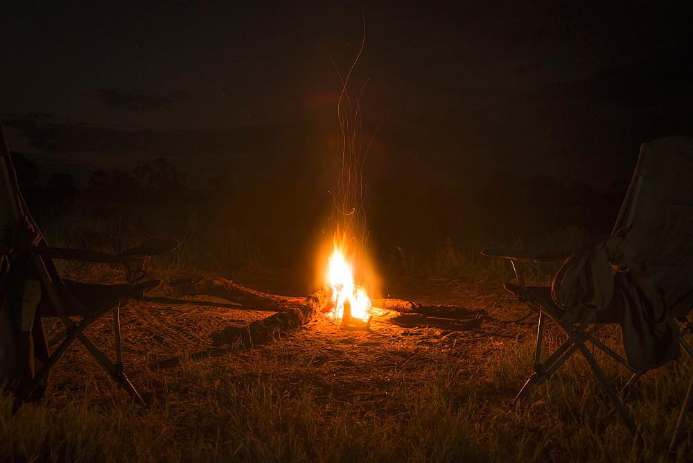 Two Camp Chairs Around Fire At Night, Botswana