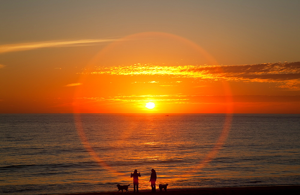 A Halo Around The Glowing Sun As It Sets Over The Ocean And An Orange Sky, Chiclana De La Frontera, Andalusia, Spain