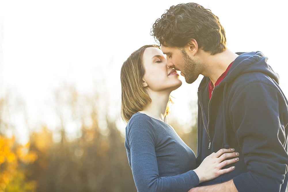 A Young Couple Holding Each Other Closely And Kissing In A City Park In Autumn, Edmonton, Alberta, Canada