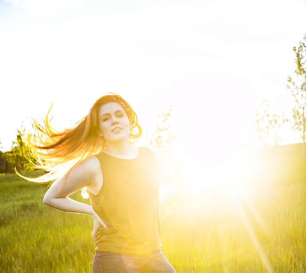Portrait of a young woman with long hair blowing behind her and a sun flare glowing beside her, Edmonton, Alberta, Canada