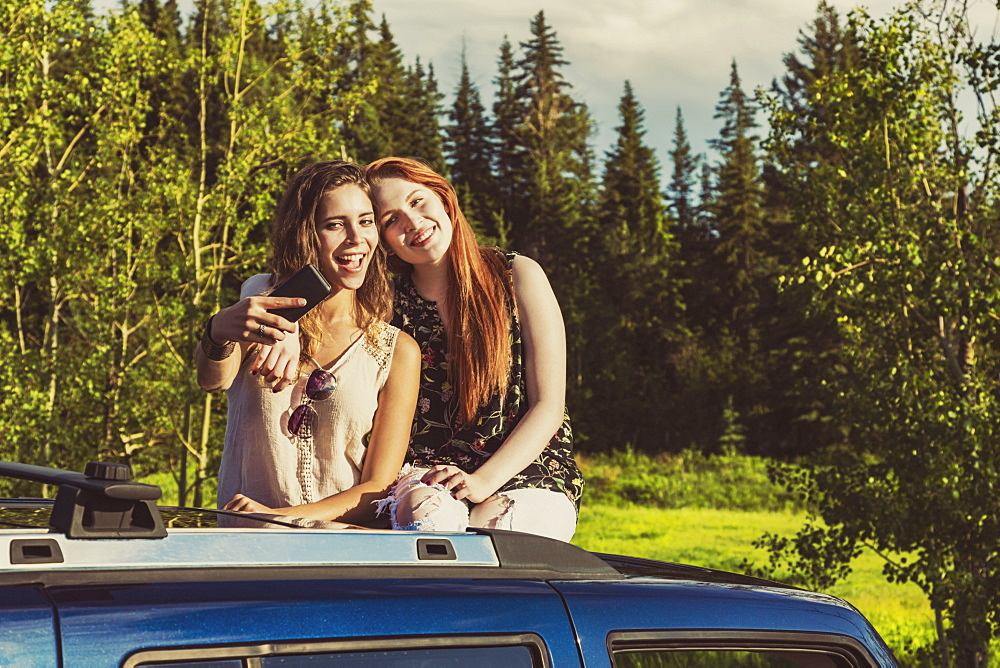 Two young women on a road trip stand up in the sunroof of a vehicle taking a self-portrait with a smart phone, Edmonton, Alberta, Canada