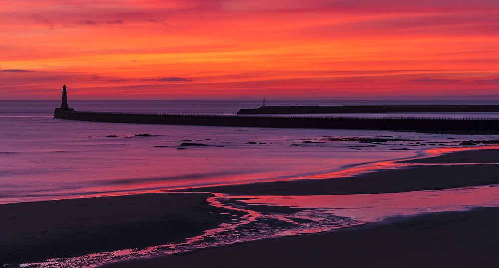 Silhouette of a pier and lighthouse with dramatic and vibrant sunrise colours in the sky and reflected in the ocean water, Sunderland, Tyne and Wear, England