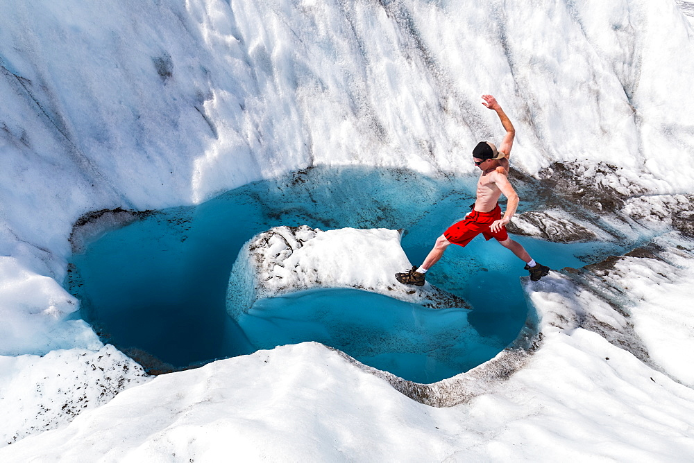 A man jumps onto an island of ice on Root Glacier in Wrangell-St. Elias National Park, Alaska, United States of America