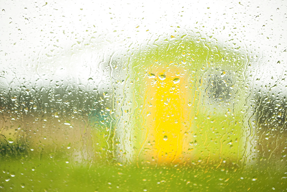 A small green building with yellow door and a window viewed through a window wet with raindrops, Newfoundland, Canada