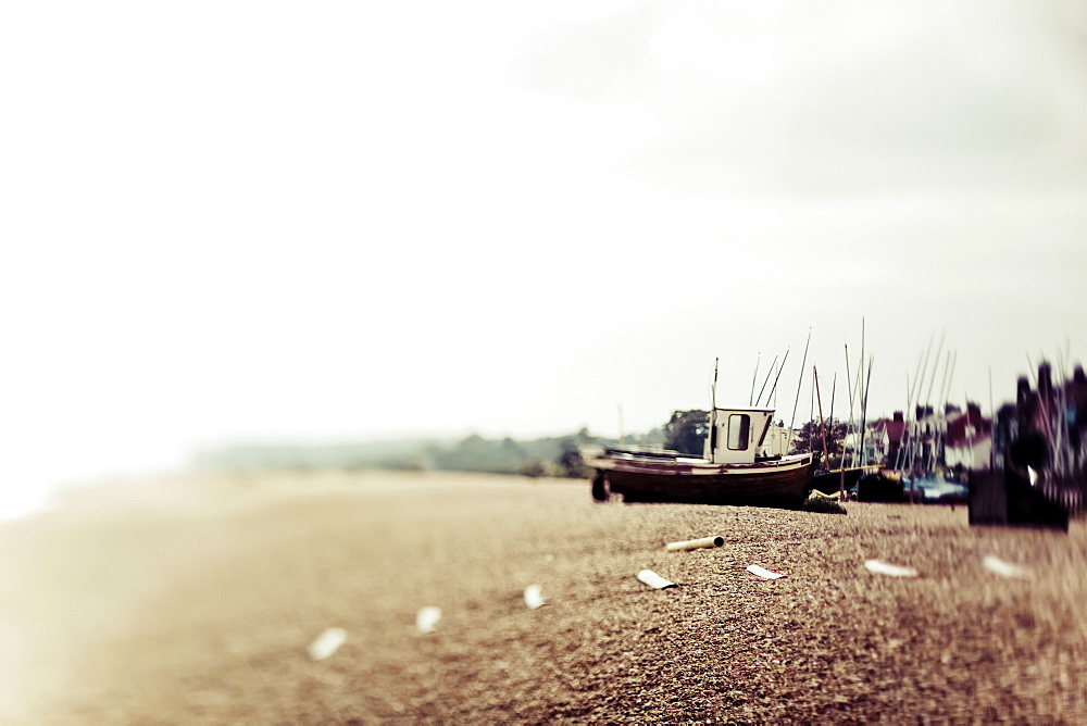 A traditional fishing boat on the shore with mist along the coast, England