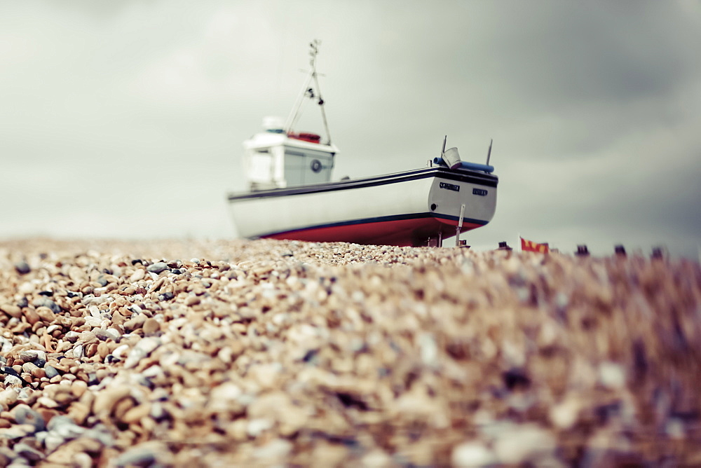 A fishing boat sits on the rocky beach under a cloudy sky, Hastings, England