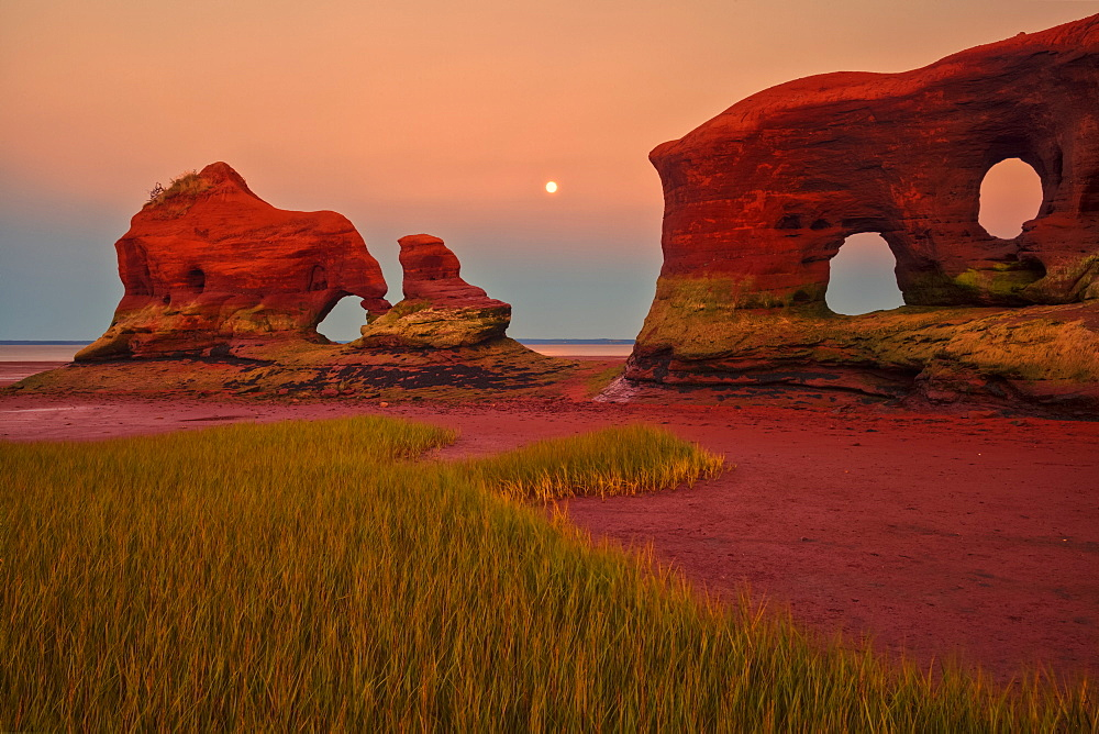 Coastal sea stacks, marsh grass and a full moon at twilight during low tide along the Minas Basin, North Medford, Nova Scotia, Canada