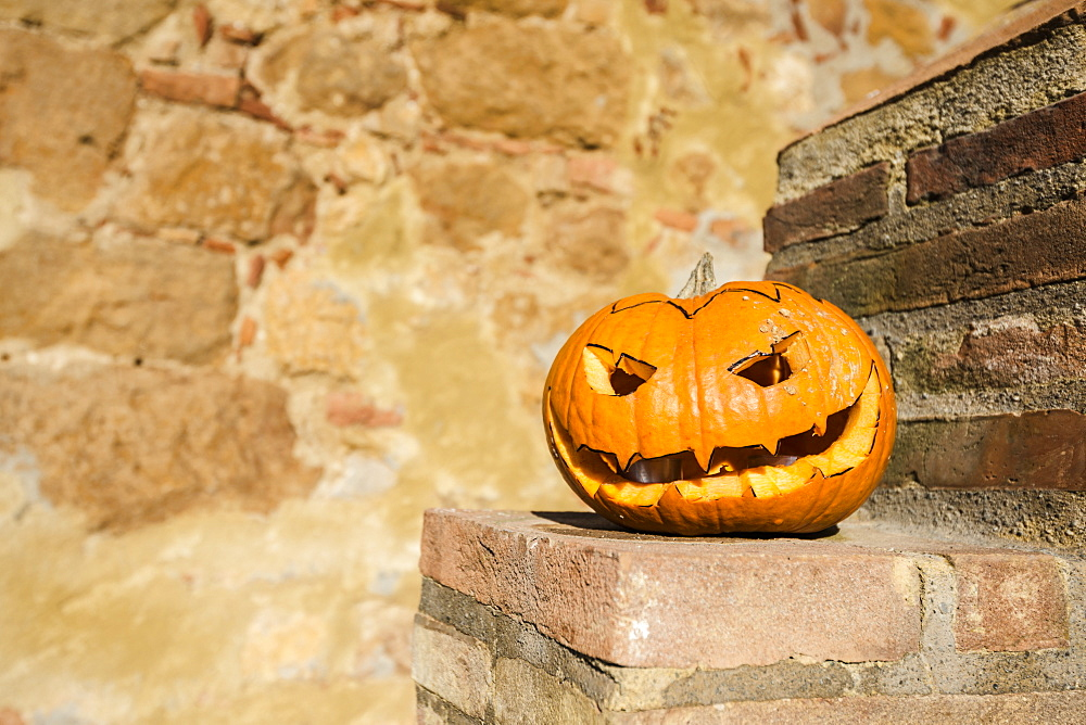 Close-Up Of A Homemade Carved Halloween Pumpkin On A Stone Wall, Pienza, Italy