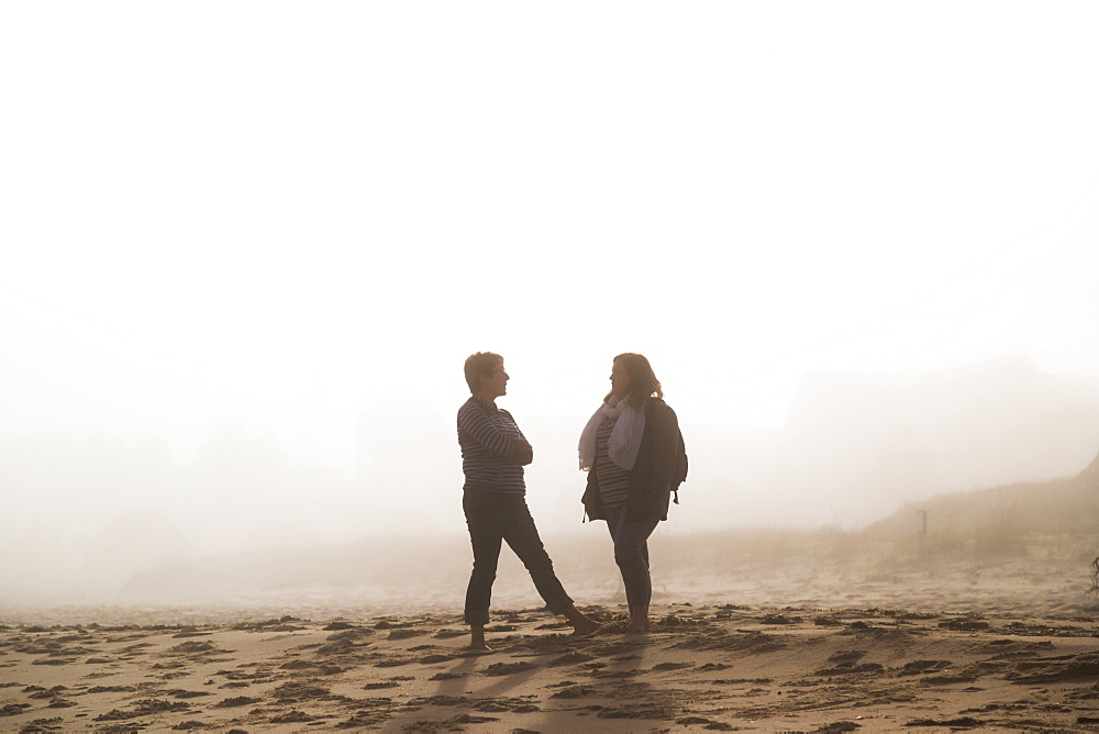 Two Female Friends Stand Talking On A Beach In The Mist, Prince Edward Island, Canada