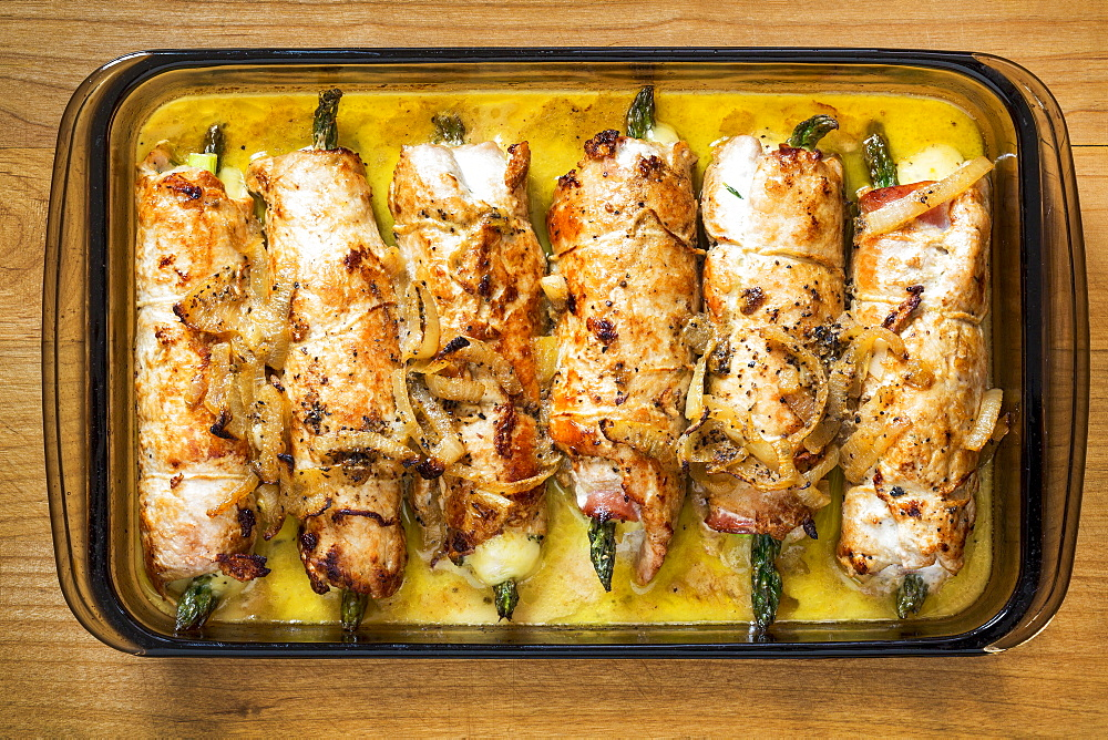 Glass Casserole Dish On Wooden Cutting Board Filled With Rolled Browned Chicken Stuffed With Asparagus In A Cream Sauce, Calgary, Alberta, Canada
