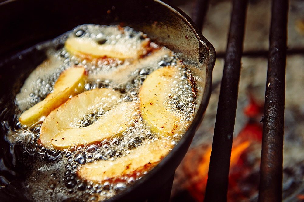 Apple Slices Being Cooked In A Frying Pan On A Grill Over An Open Flame, Ontario, Canada