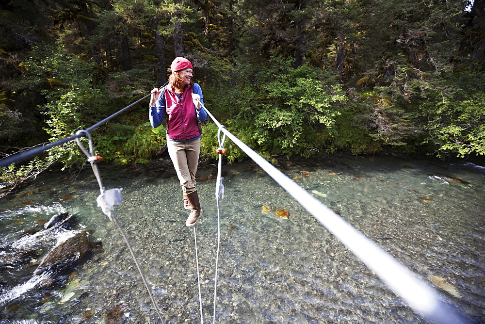 A Woman Walks On A Cable On A Suspension Bridge Over A River, Alaska, United States Of America