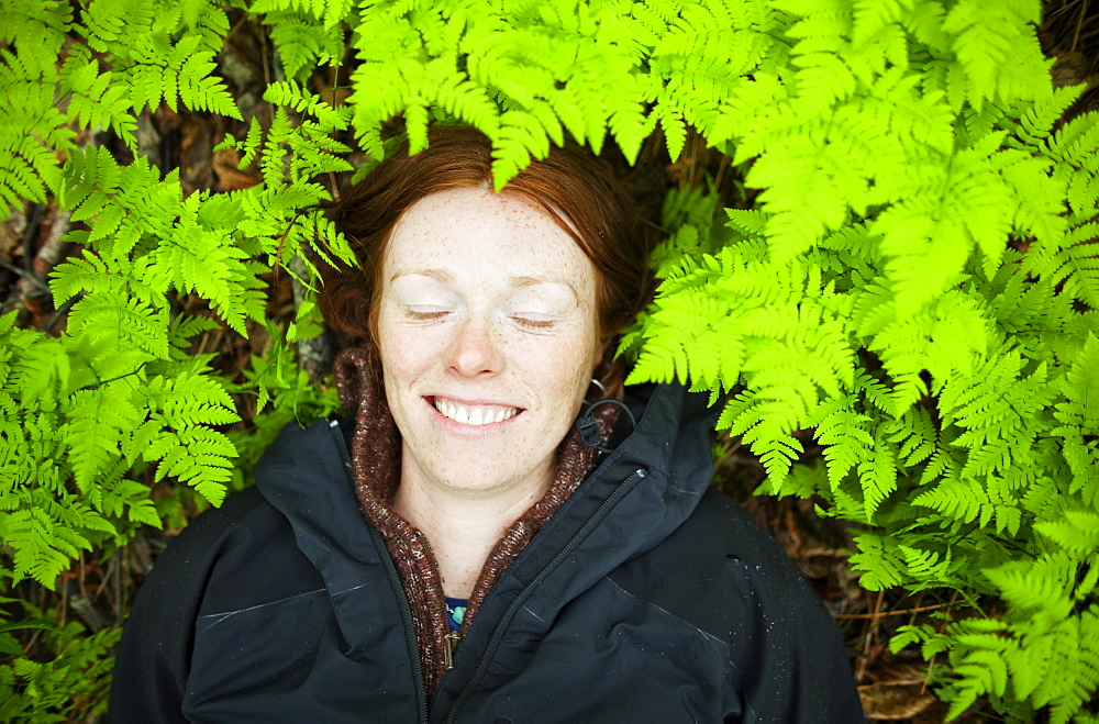 A Woman Lays Her Head On The Forest Floor Among The Bright Green, Lush Ferns, Alaska, United States Of America