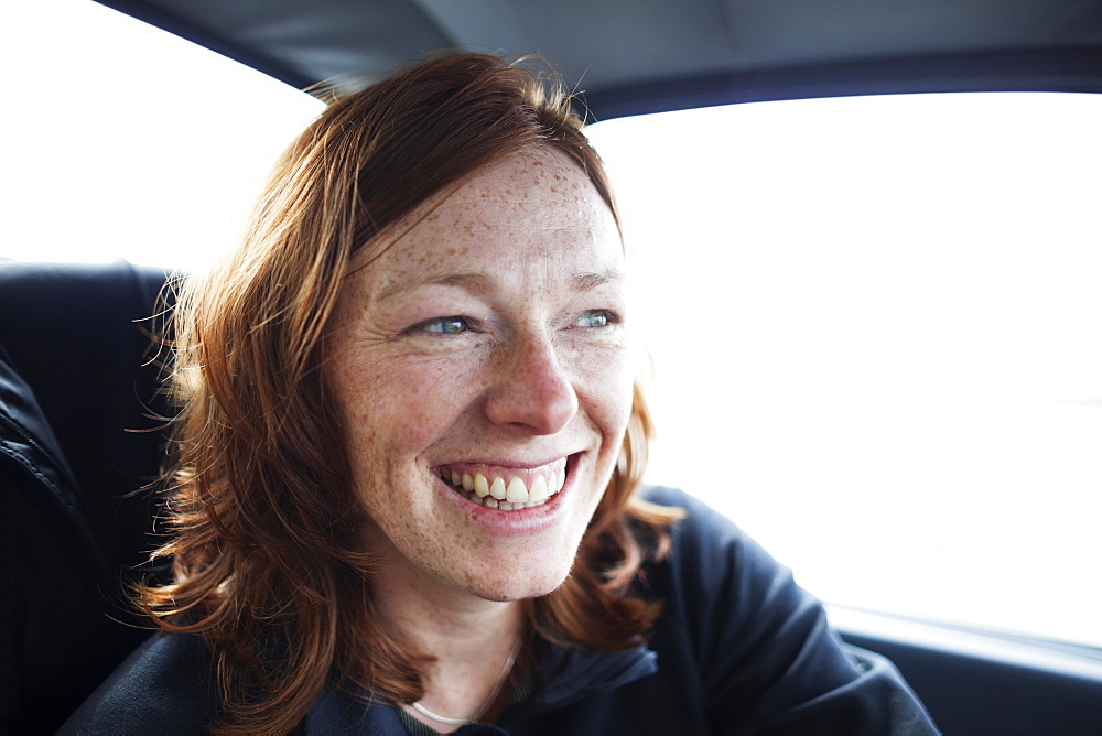 A Woman With Red Hair And Freckles Smiling While Riding In A Car, Alaska, United States Of America