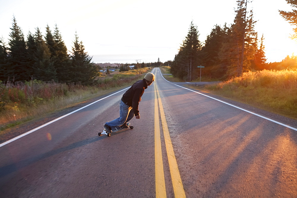 A Young Man Skateboarding Down A Road At Dusk, Homer, Alaska, United States Of America