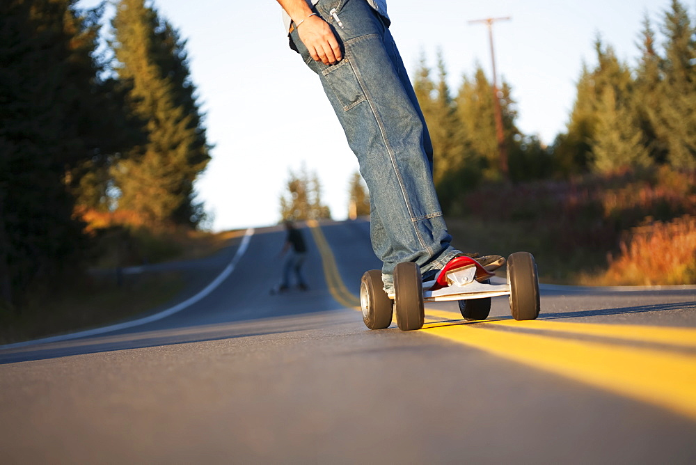 Young Men Skateboarding Down A Road, Homer, Alaska, United States Of America