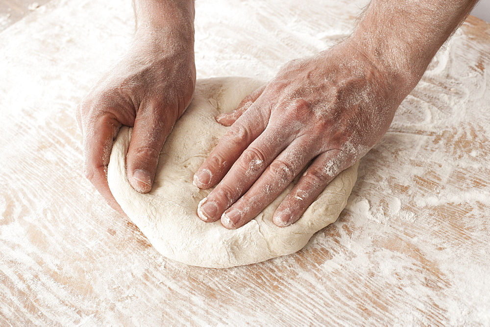 Hands Working With Pizza Dough On A Wooden Floured Surface
