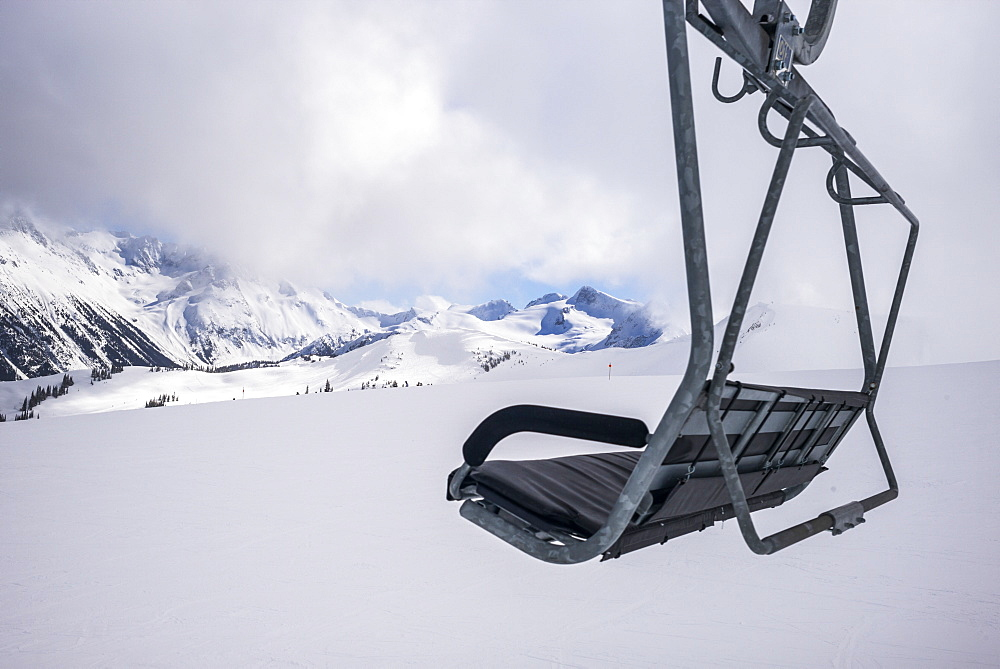 A Chairlift Over The Snow With A View Of The Snow Covered Canadian Rocky Mountains In A Ski Resort, Whistler, British Columbia, Canada