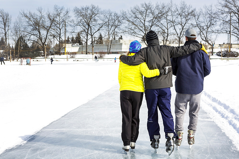 Two Males And One Female Skating Arm In Arm On Freshly Groomed Ice On Pond With Community Centre In The Background, Calgary, Alberta, Canada