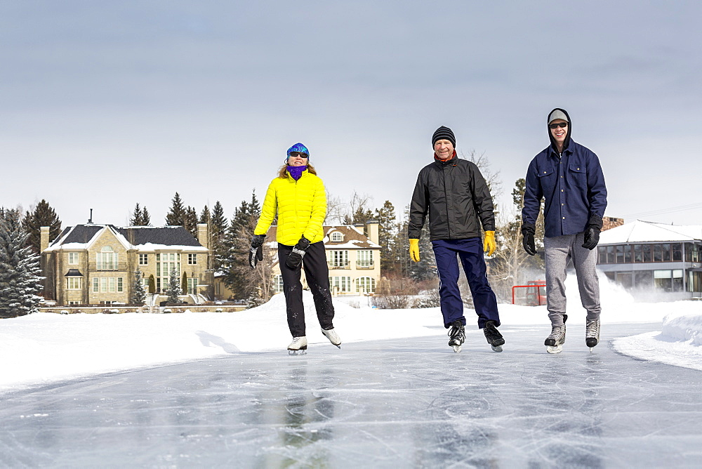 Two Males And One Female Skating On Freshly Groomed Ice On Pond With Houses In The Background, Calgary, Alberta, Canada