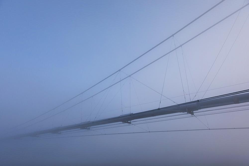 The Trans-Alaska Pipeline Appears Through Fog Where It Crosses The Tanana River On A Subzero Morning, Alaska, United States Of America