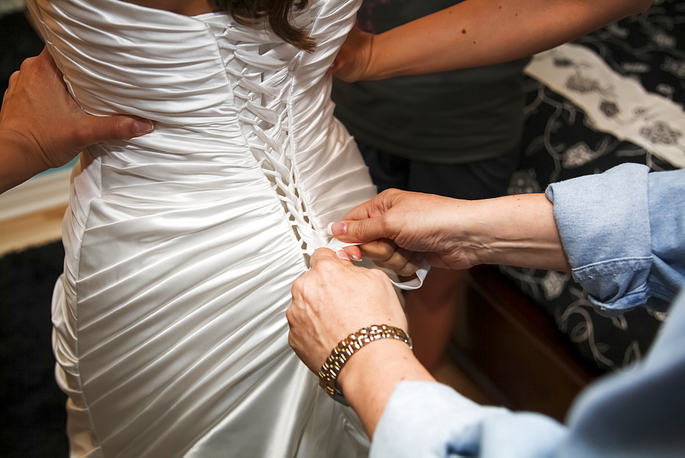 A Woman Helps Dress A Bride On Her Wedding Day, Ontario, Canada