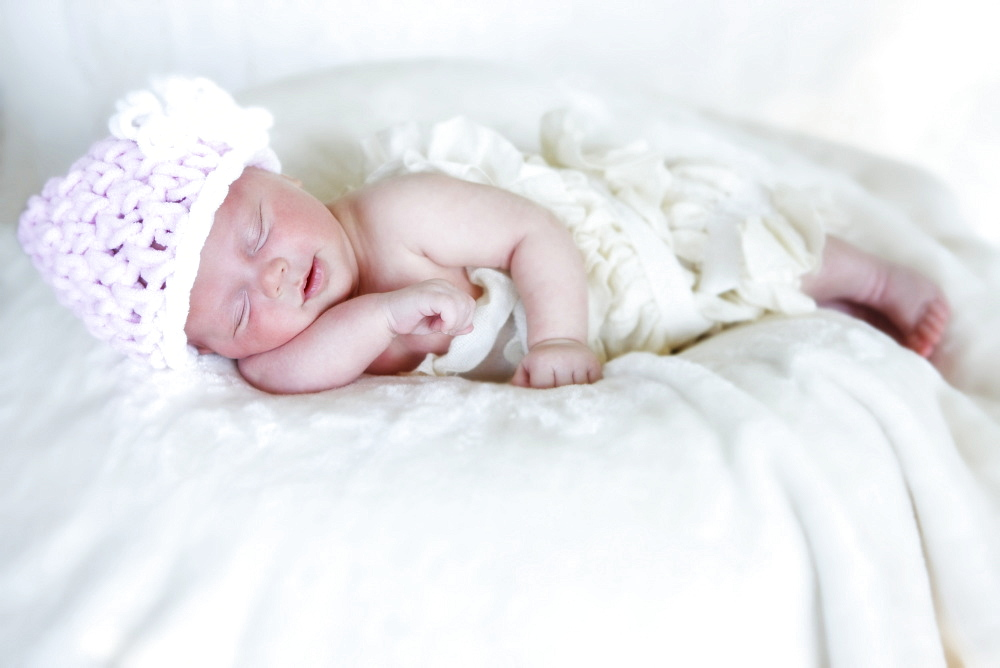 A Newborn Baby Lays Sleeping On A White Blanket Wearing A Pink Knit Hat, Washington, United States Of America