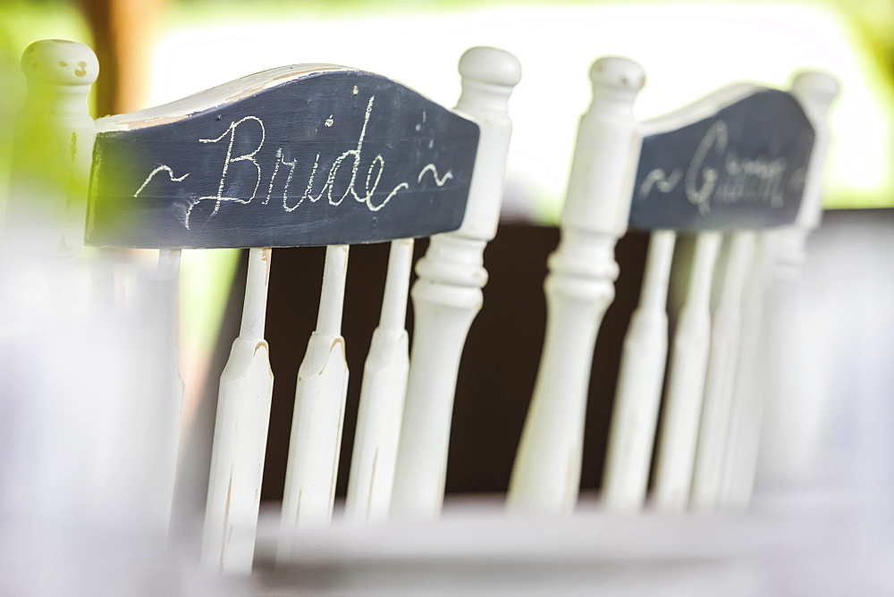 White Wooden Chairs Side By Side With Bride And Groom Written In Chalk On A Chalkboard Finish On The Back