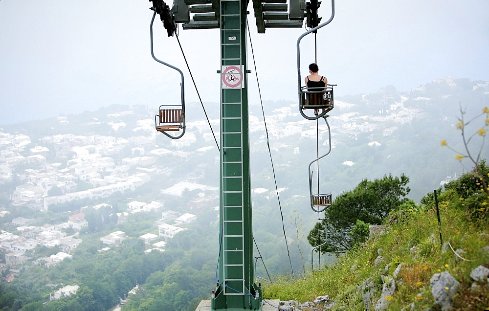 Capri, Italy; Woman Riding Chairlift To The Top Of Monte Solaro