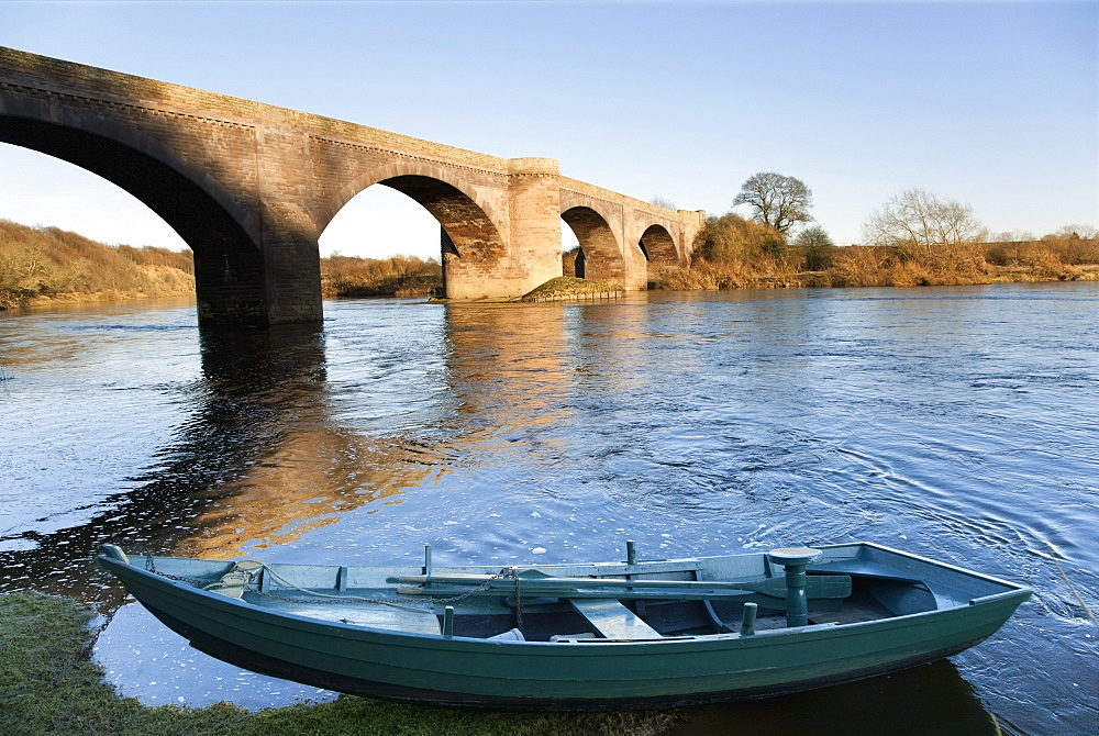 Northumberland, England; A Boat Moored On The Edge Of A River With A Bridge