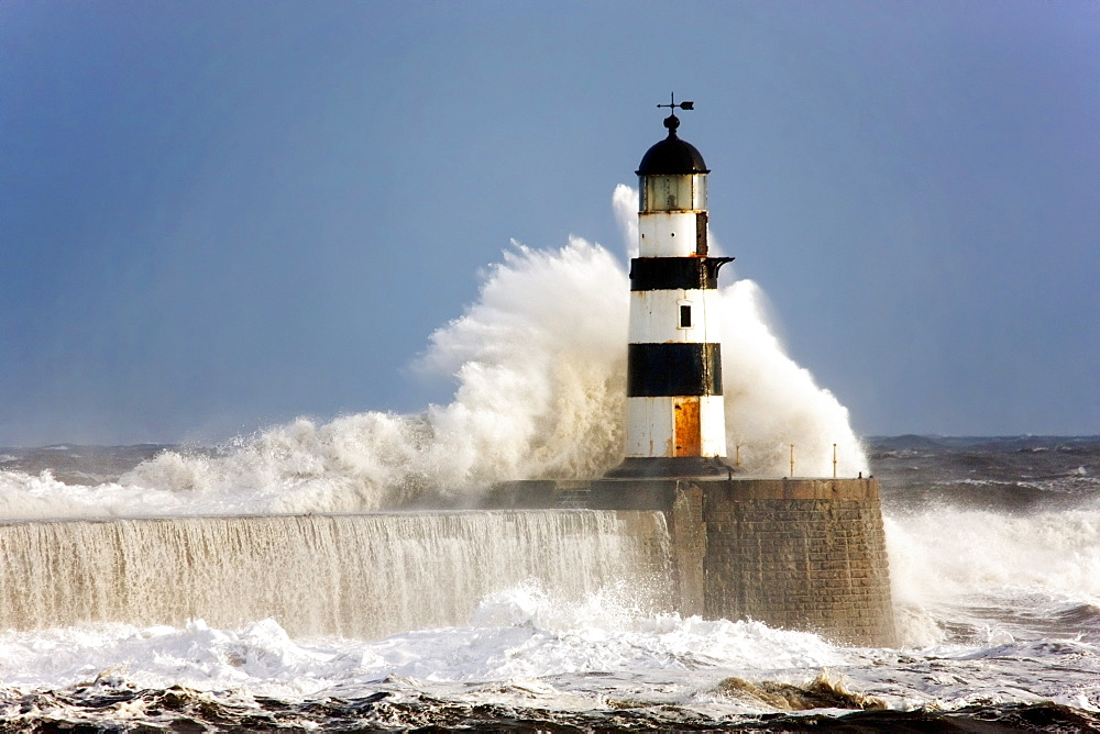 Seaham, Teesside, England; Waves Crashing Against A Lighthouse