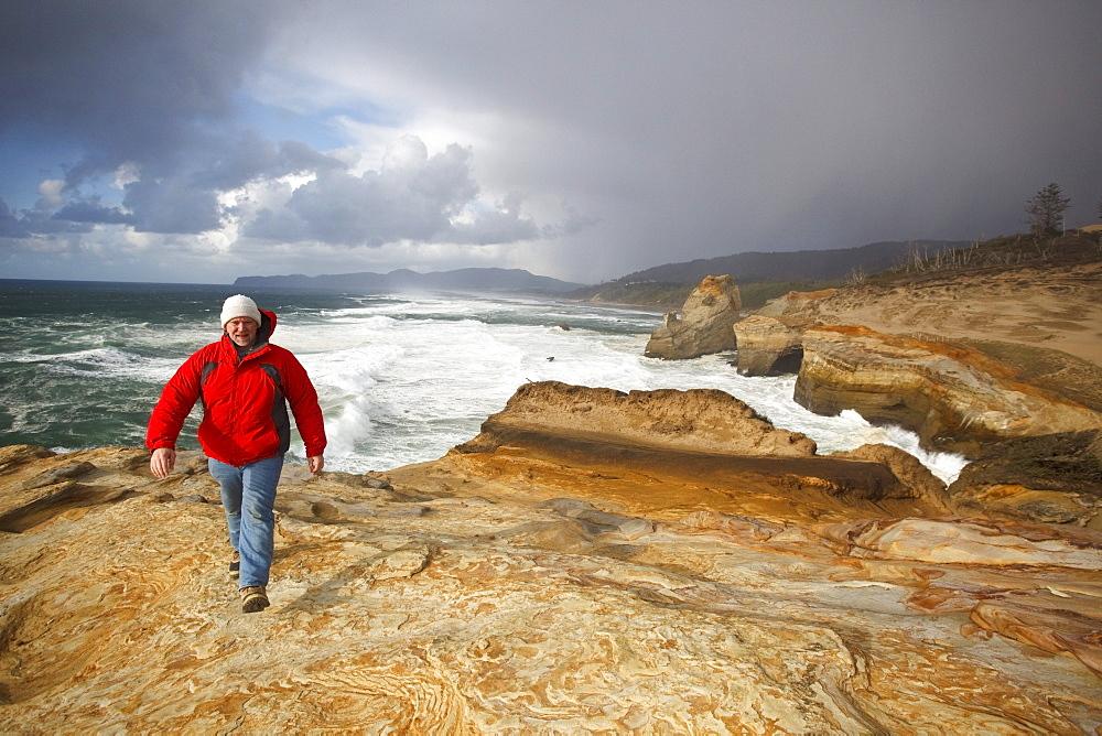 Pacific City, Oregon, United States Of America; A Man Walking Along The Coast At Cape Kiwanda