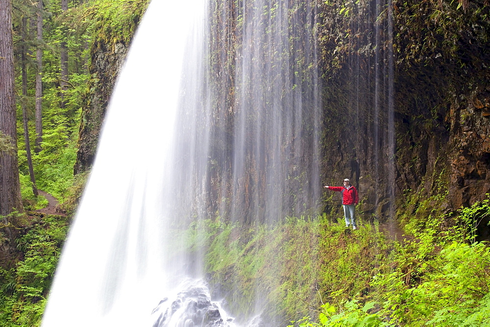 Oregon, United States Of America; A Person Reaching Out To Touch As They Stand Behind North Middle Falls In Silver Falls State Park