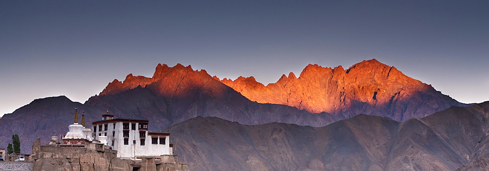 A Building On A Rock Ledge With Alpenglow Over The Mountains In The Background; Lamayuru Ladakh India