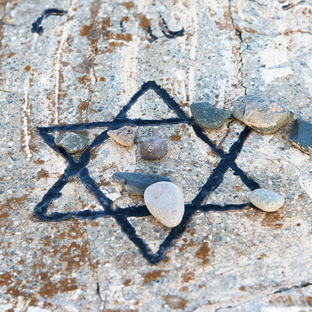 A star of david etched and painted on a rock with stones laying on it