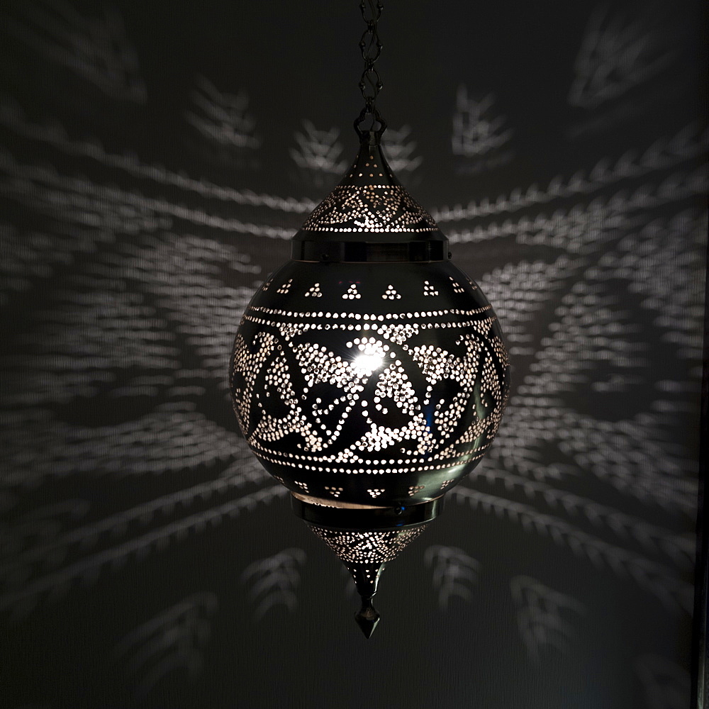 Illuminated hanging light fixture reflecting pattern on the wall, Istanbul turkey