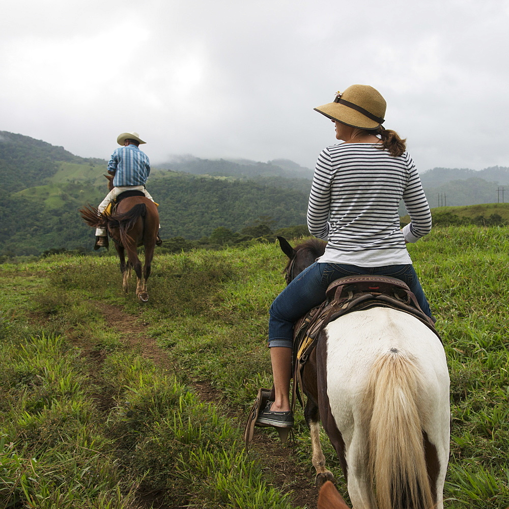 A Man And Woman Riding Horseback Through The Hills, Zacapa, Guatemala
