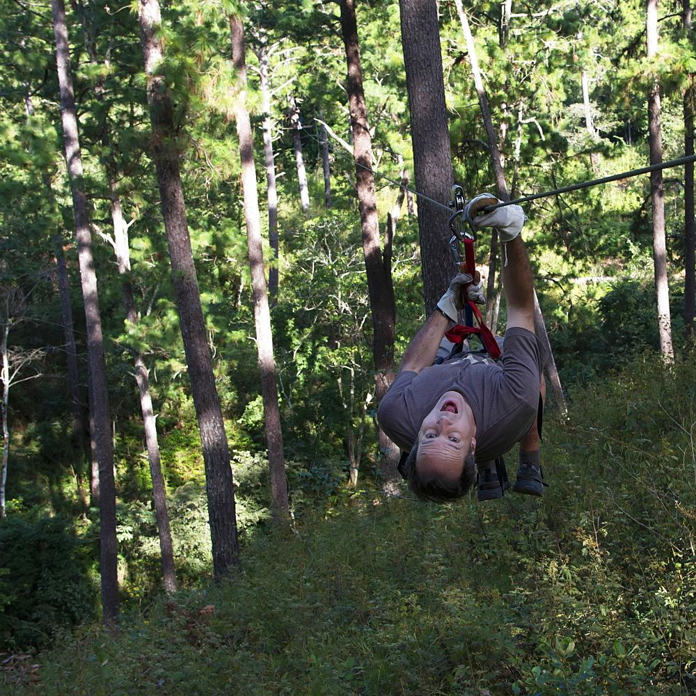 A Man Hangs Upside Down On A Zip-Line, Copan, Honduras