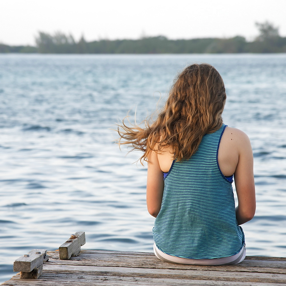 A Girl Sits On The Edge Of A Dock, Utila, Bay Islands, Honduras