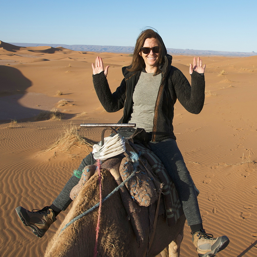 A woman riding a camel with no hands being silly, Souss-massa-draa morocco