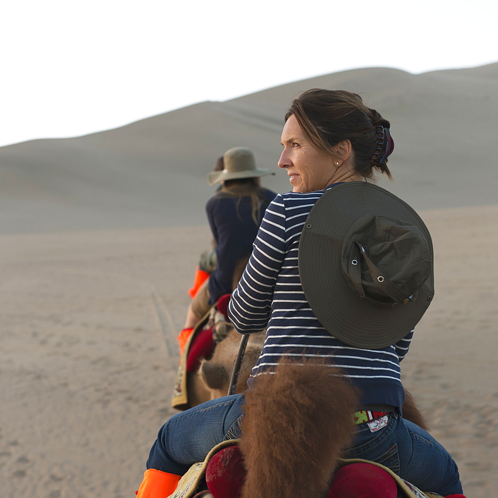 A woman and her daughters riding camels on a desert landscape, Jiuquan gansu china