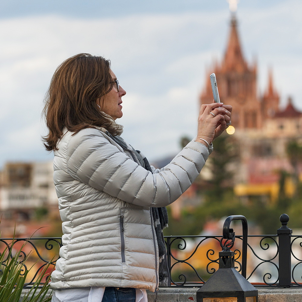 Woman Taking A Photograph With A Smart Phone And A Church In The Distance, San Miguel De Allende, Guanajuato, Mexico