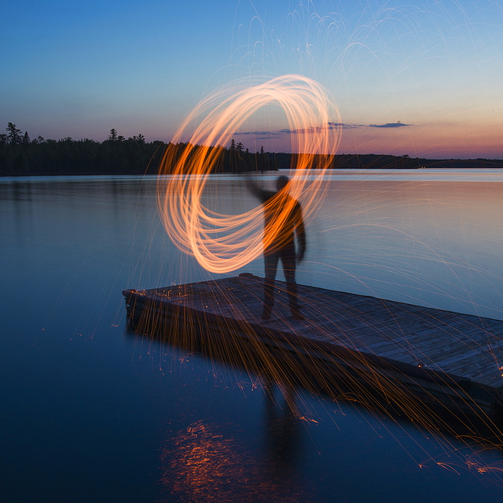 A Man Stands On The End Of A Dock At Sunrise Moving A Glowing Light In A Circular Form, Ontario, Canada