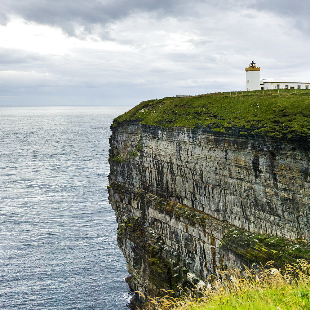 Duncansby Head Lighthouse On The Edge Of A Cliff On The Coast Under A Cloudy Sky, Scotland