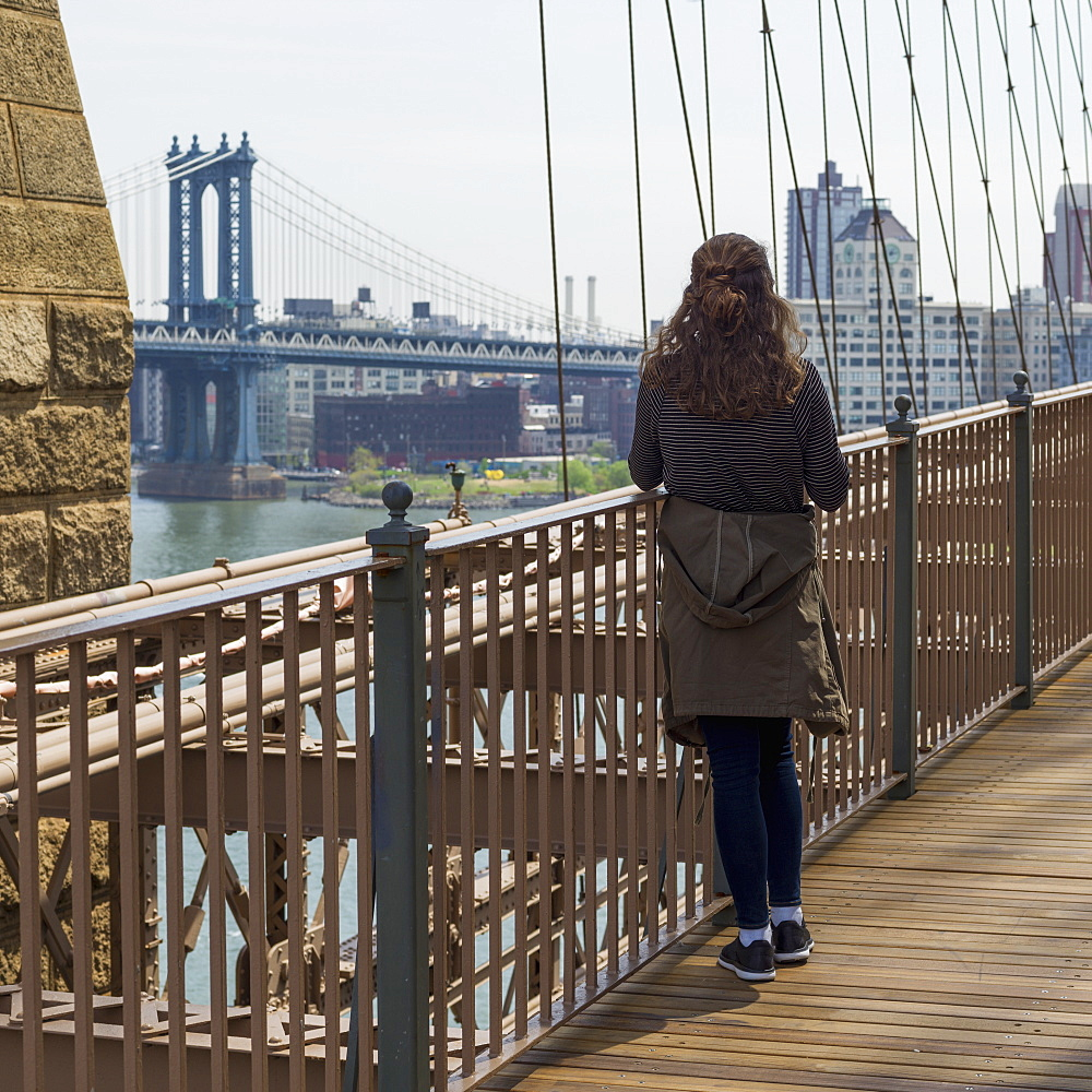 A Young Woman Stands On The Brooklyn Bridge Looking Out Over The East River To The Manhattan Bridge, New York City, New York, United States Of America
